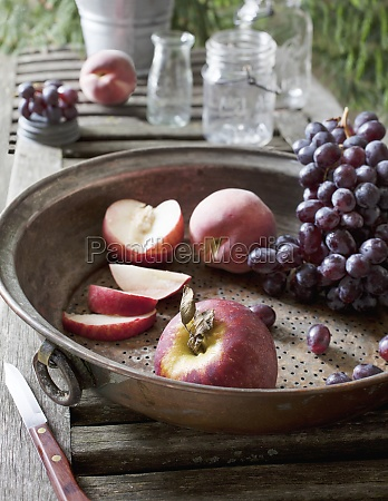 metal sieve with grapes apple and