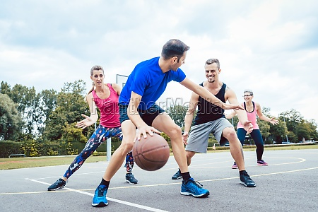 basketball players playing at outdoors court