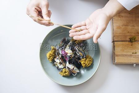 a chef garnishing a mussel dish