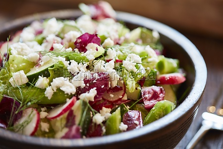 a mixed salad with radishes cucumber