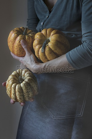 woman holding three tiny pumpkins while