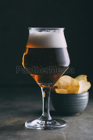 glass of dark beer and chips