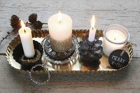 four burning candles with christmas decorations