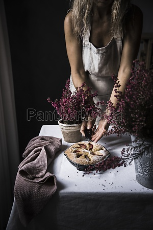 woman cook in apron cutting plum