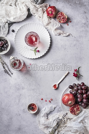 different utensils and pomegranate with grapes