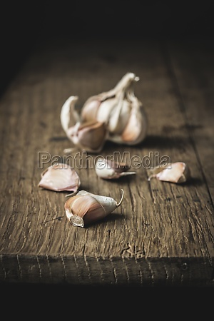 unpeeled garlic on rough wooden table