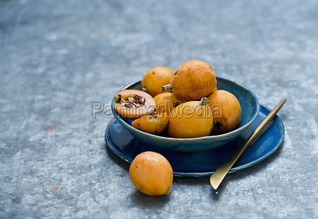 medlar fruits in blue bowl