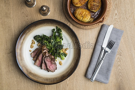 beef steak with broccolini and hasselback