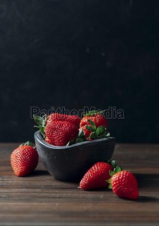 fresh ripe strawberries in black concrete