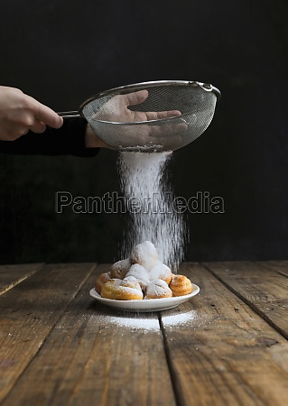 cook sieving sugar powder on top