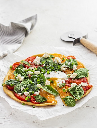 socca pizza with spinach tomatoes and