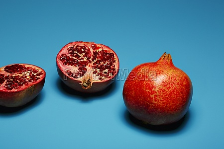 whole and halved pomegranates in front