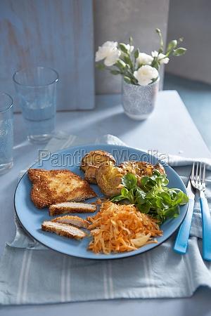 pork schnitzel with crushed potatoes sauerkraut