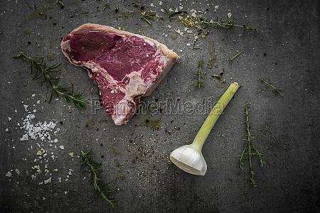 raw t bone steak rosemary thyme