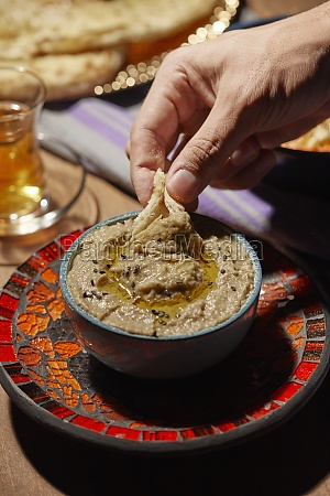 dipping piece of bread in baba
