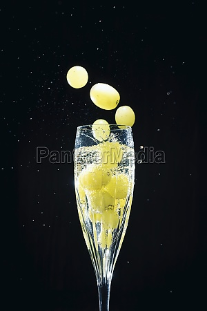 grapes falling in glass of champagne