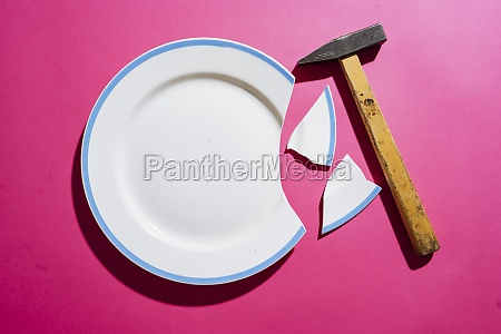 broken white plate on pink background