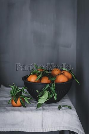 orange tangerines in ceramic ornamental bowl