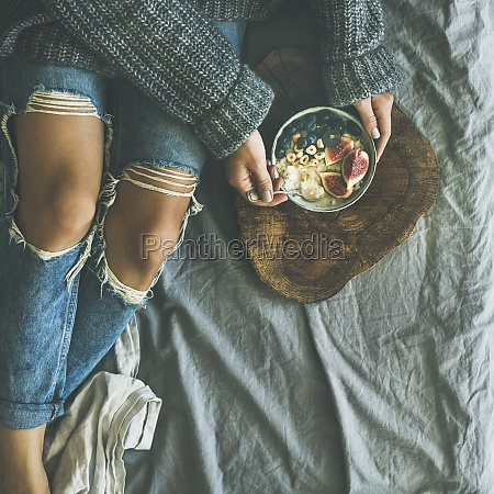 woman in sweater and jeans eating