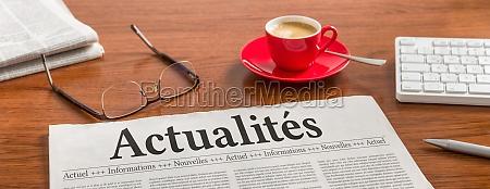 a newspaper on a wooden desk
