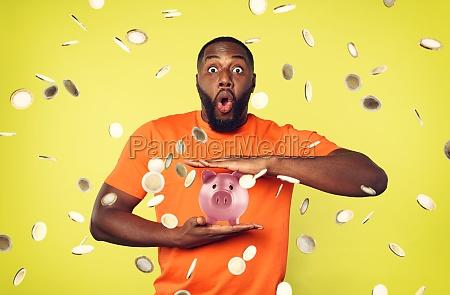 man under coins rain holds a
