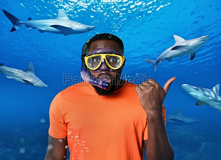 scared man with mask underwater surrounded