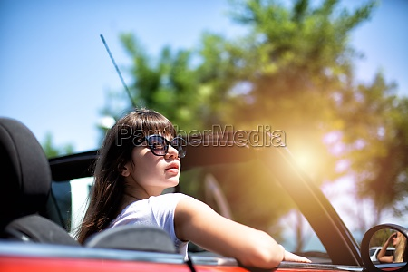young woman in cabriolet car departs