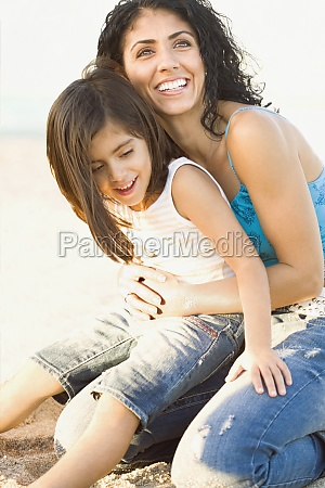 mixed race mother holding daughter in