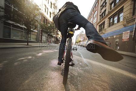 caucasian man riding bicycle on urban