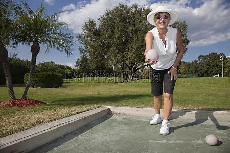 senior caucasian woman playing bocce ball