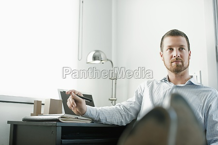 caucasian businessman sitting at desk with
