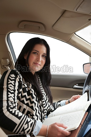 young woman in car with notebook