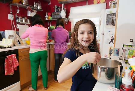 girl in kitchen with mother and