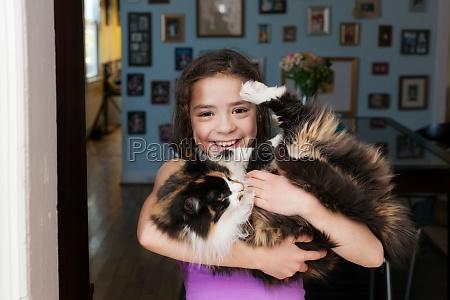 girl holding pet cat
