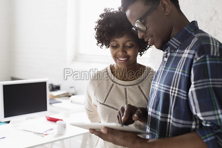 young man and woman using digital