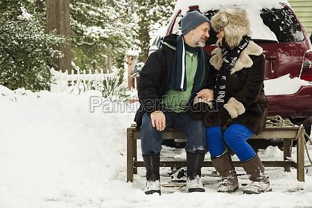 mature couple sitting on toboggan in