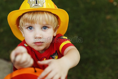 boy wearing firemans helmet