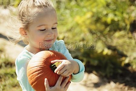 girl carrying pumpkin