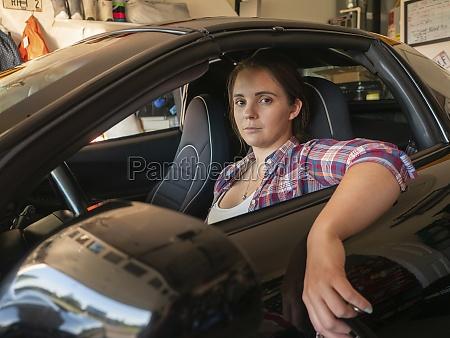 woman sitting in car in garage