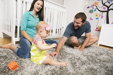 mid adult couple playing with baby