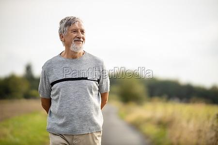happy senior man walking outdoors on