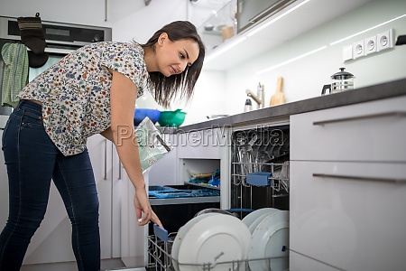 pretty young woman washing dishes in