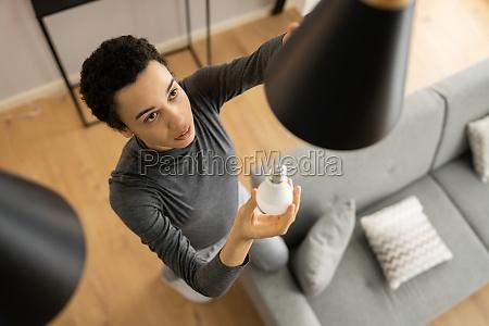 african american replacing broken light bulb
