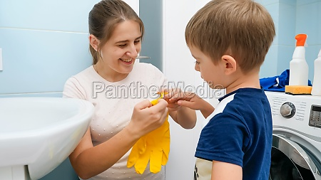 smiling young mother helping little son