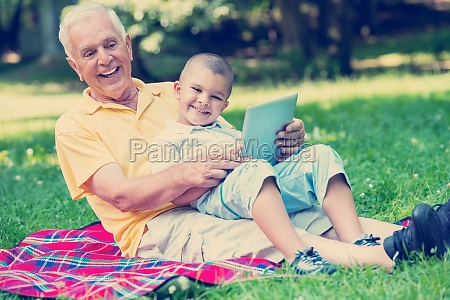 grandfather and child in park using