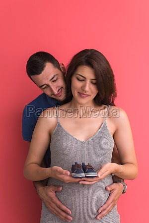 young pregnant couple holding newborn baby
