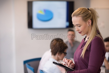 blonde businesswoman working on tablet at