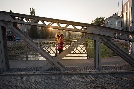 woman jogging across the bridge at