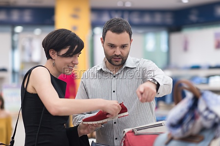 couple chooses shoes at shoe store