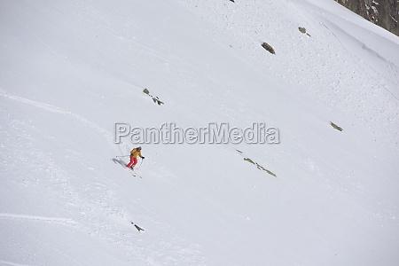 freeride skier skiing in deep powder